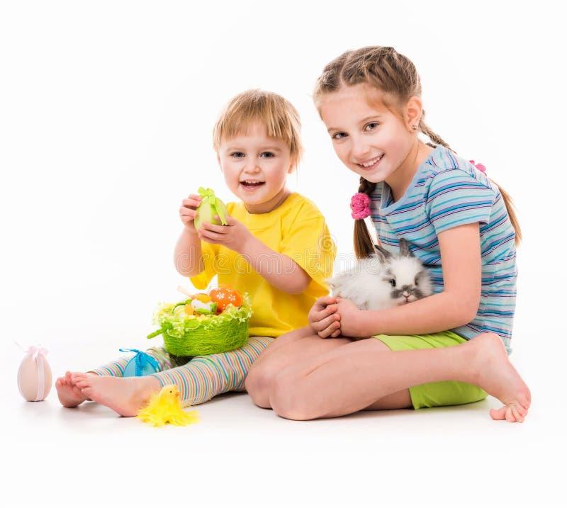 lyckliga små systrar med henne kanin arkivfoton