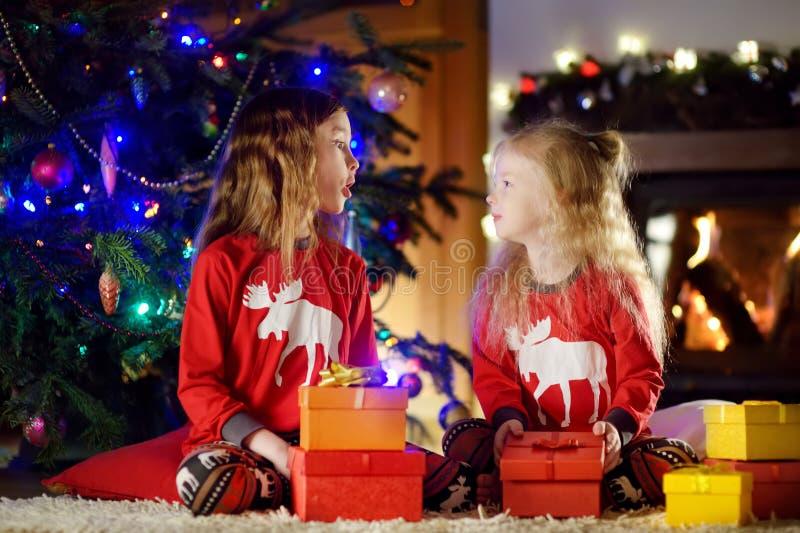 Lyckliga små systrar som bär julpyjamas som spelar vid en spis i en hemtrevlig mörk vardagsrum på julhelgdagsafton arkivbilder
