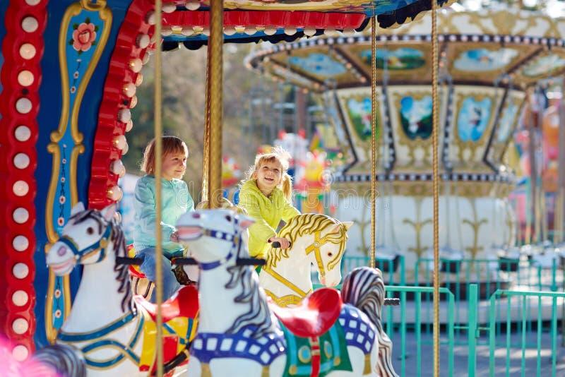 Lyckliga små systrar som rider på karusell arkivbilder