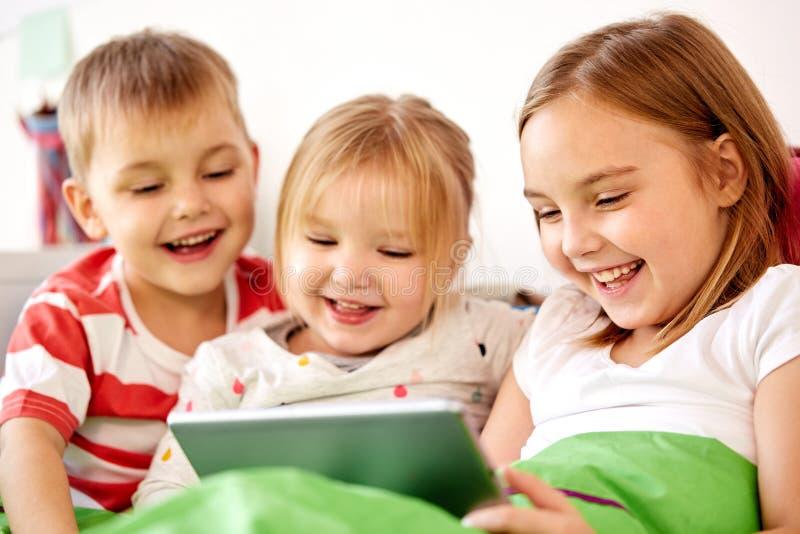 Lyckliga små ungar med minnestavlaPC i säng hemma fotografering för bildbyråer