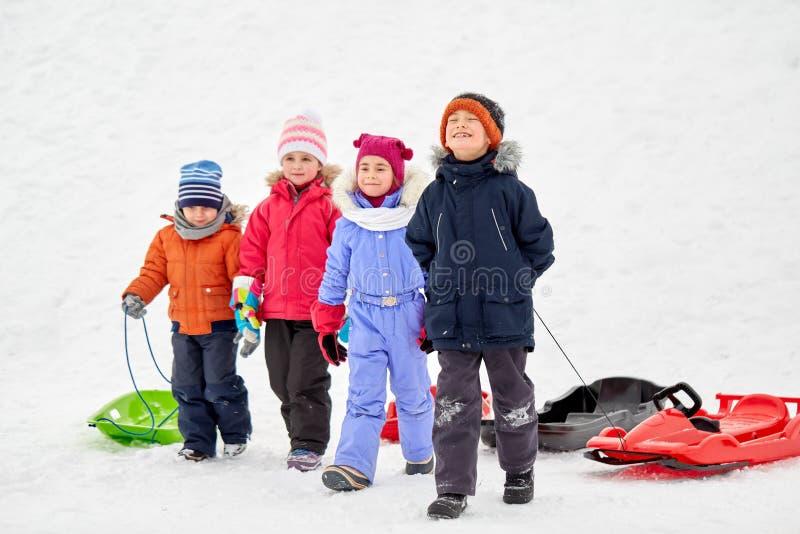 Lyckliga små ungar med slädar i vinter fotografering för bildbyråer