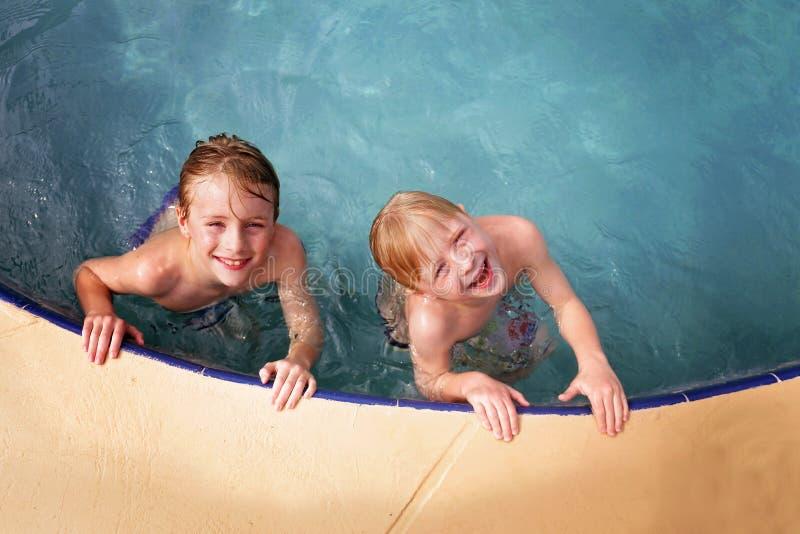 Lyckliga små ungar som ler, som de simmar i familjsimbassängen arkivbilder