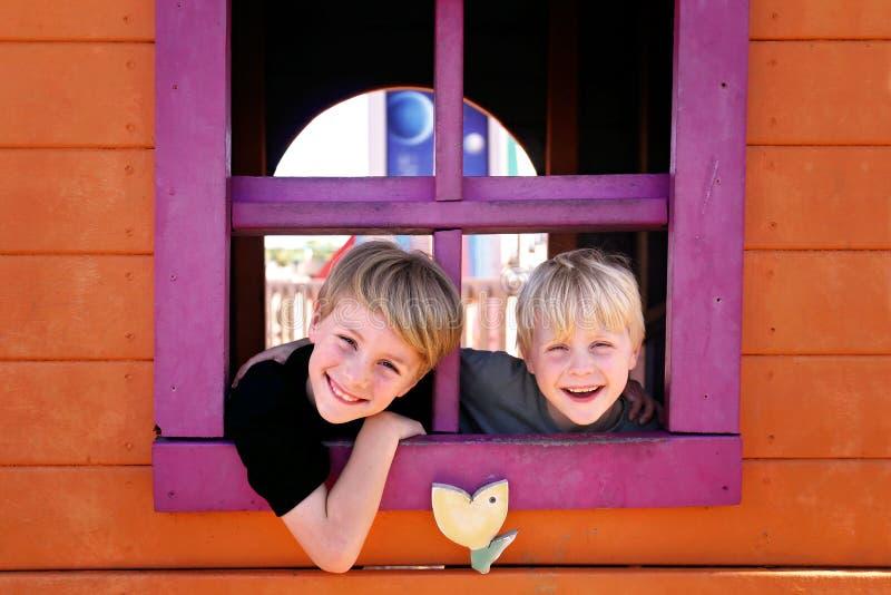 Lyckliga små ungar som ler på, parkerar, som de kikar ut fönstret av ett klubbhusfort arkivfoto