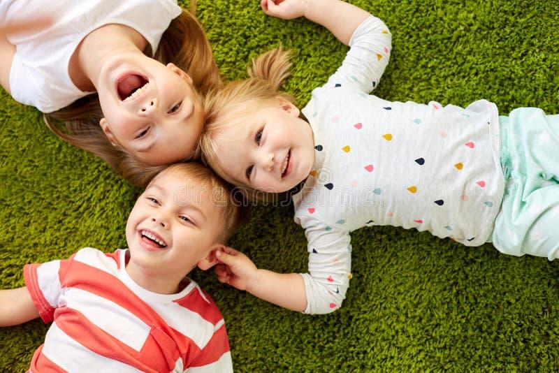 Lyckliga små ungar som ligger på golv eller matta fotografering för bildbyråer