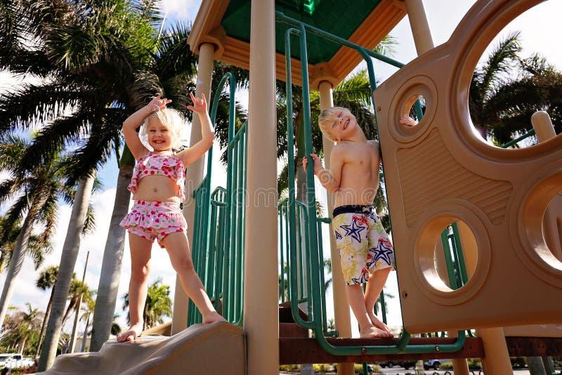 Lyckliga små ungar som spelar på lekplats på stranden royaltyfria bilder