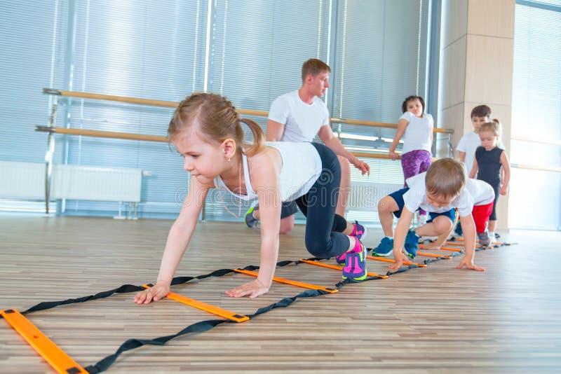 Lyckliga sportiga barn i idrottshall Ungeövningar fotografering för bildbyråer