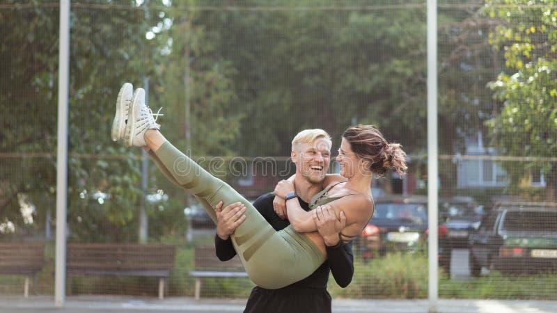 Lyckliga sportiga par efter bra utbildning på en sportsground arkivbild