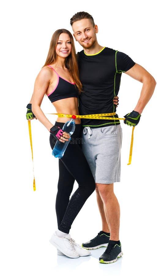 Lyckliga sportpar - man och kvinna med att mäta bandet på when arkivfoton