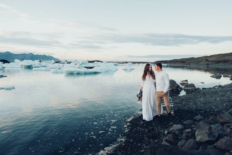 Lyckliga stilfulla le par som går och kysser i Island, på royaltyfri foto