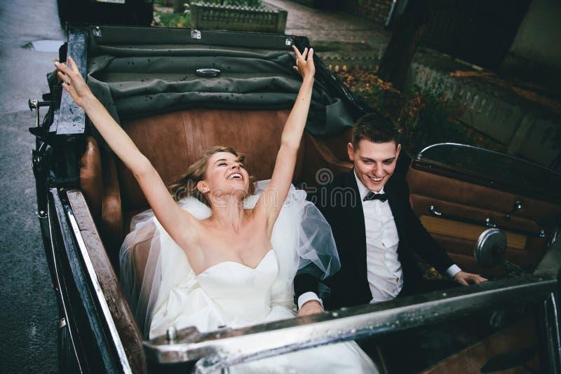Lyckliga stilfulla nygift personpar som poserar i en retro bil royaltyfria bilder