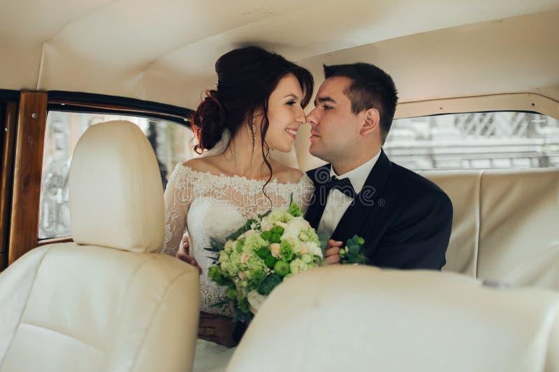 Lyckliga stilfulla nygift personpar som poserar i retro bil royaltyfria foton