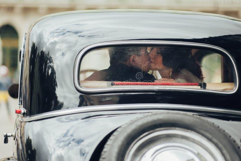 Lyckliga stilfulla nygift personpar som poserar i retro bil royaltyfri fotografi