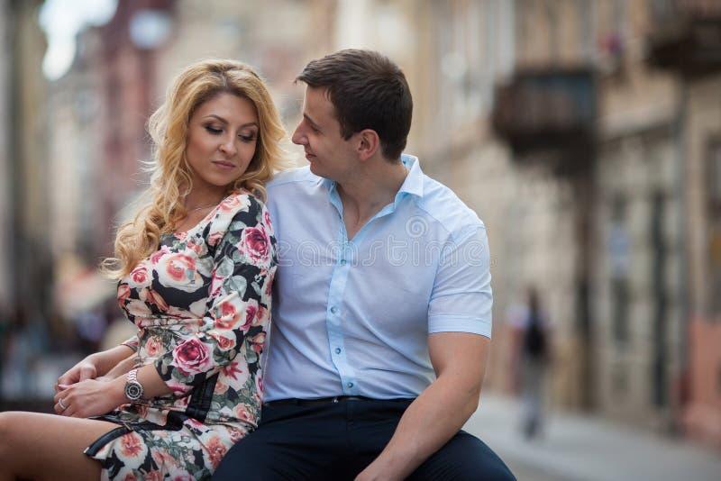 Lyckliga stilfulla nygift personpar som poserar på träbänk i stad royaltyfri fotografi