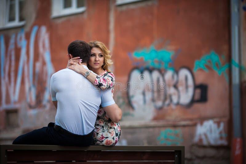 Lyckliga stilfulla nygift personpar som poserar på träbänk i stad arkivfoto