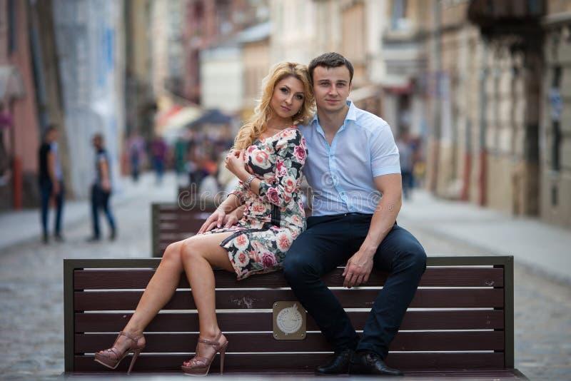 Lyckliga stilfulla nygift personpar som poserar på träbänk i stad arkivbilder