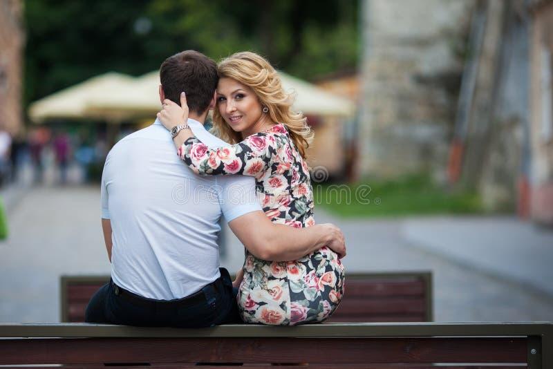 Lyckliga stilfulla nygift personpar som poserar på träbänk i stad royaltyfri foto