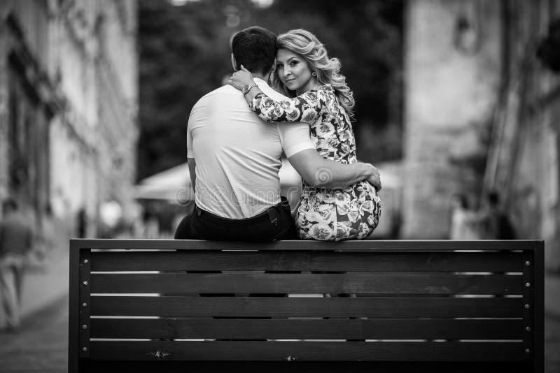 Lyckliga stilfulla nygift personpar som poserar på träbänk i stadb& arkivfoto