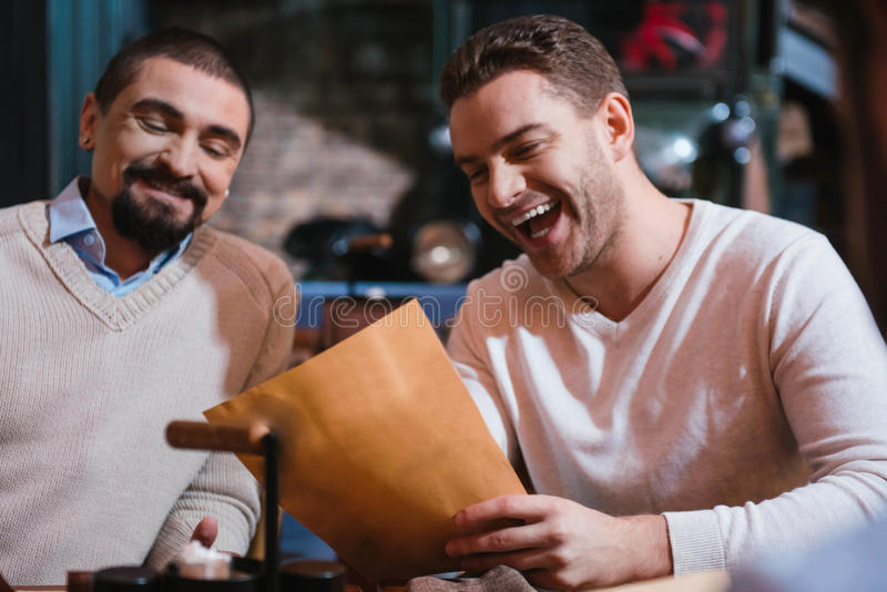 Lyckliga stiliga män som ser menyn royaltyfri bild