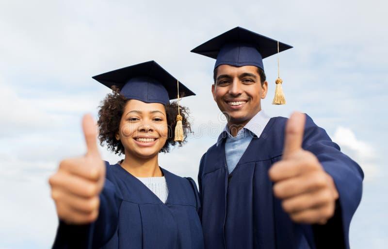 Lyckliga studenter eller ungkarlar som visar upp tummar arkivfoto