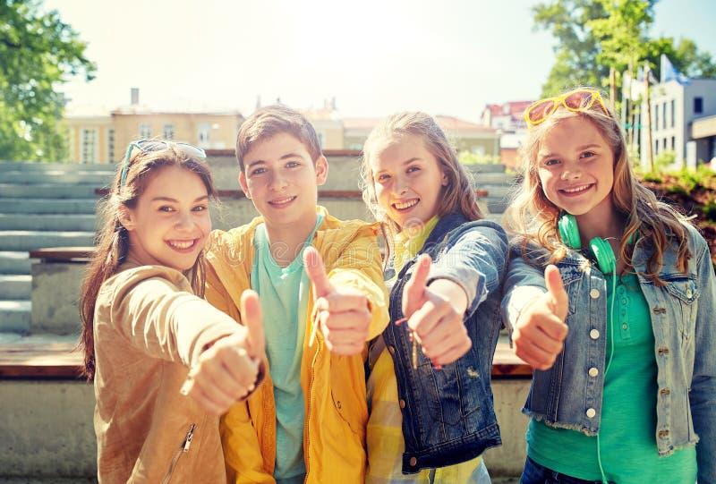 Lyckliga studenter eller vänner som visar upp tummar royaltyfri bild