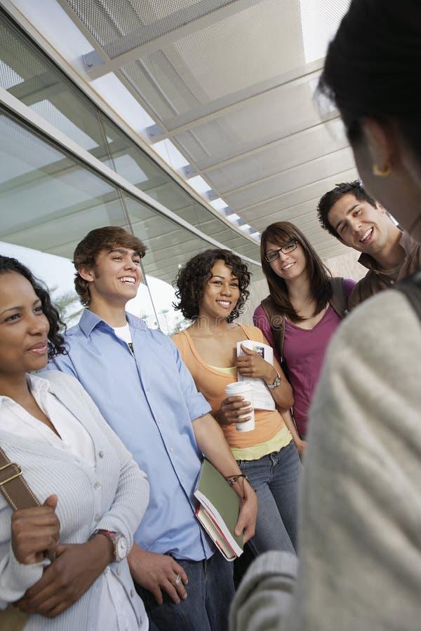 Lyckliga studenter som ser läraren arkivfoto