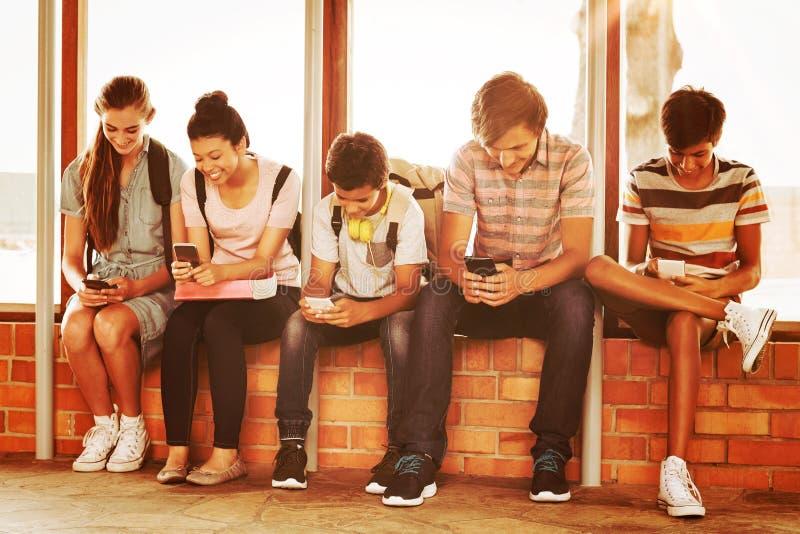 Lyckliga studenter som sitter på fönsterfönsterbräda och använder mobiltelefonen i korridor arkivfoton