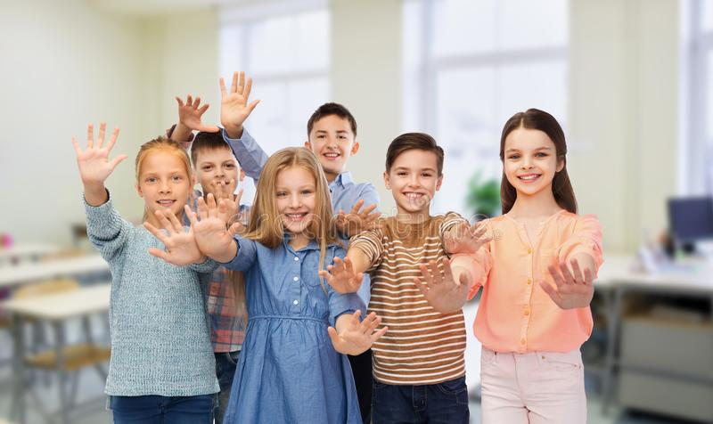 Lyckliga studenter som vinkar händer på skolan royaltyfria foton