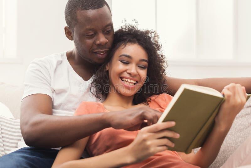 Lyckliga svarta par som tillsammans hemma läser royaltyfri foto
