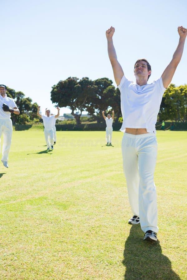 Lyckliga syrsaspelare som tycker om seger, medan stå på fält fotografering för bildbyråer