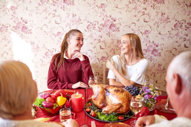Lyckliga systrar på den festliga tacksägelsematställen för familj på en ljus bakgrund Inhemskt fira begrepp royaltyfria foton