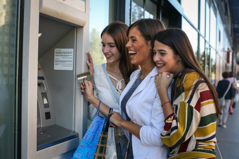 Lyckliga tagande pengar för vänner från ATM-maskinen royaltyfria bilder