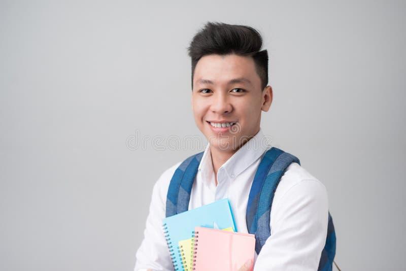 Lyckliga tillfälliga asiatiska innehavböcker för manlig student som isoleras på en grå färg royaltyfri bild