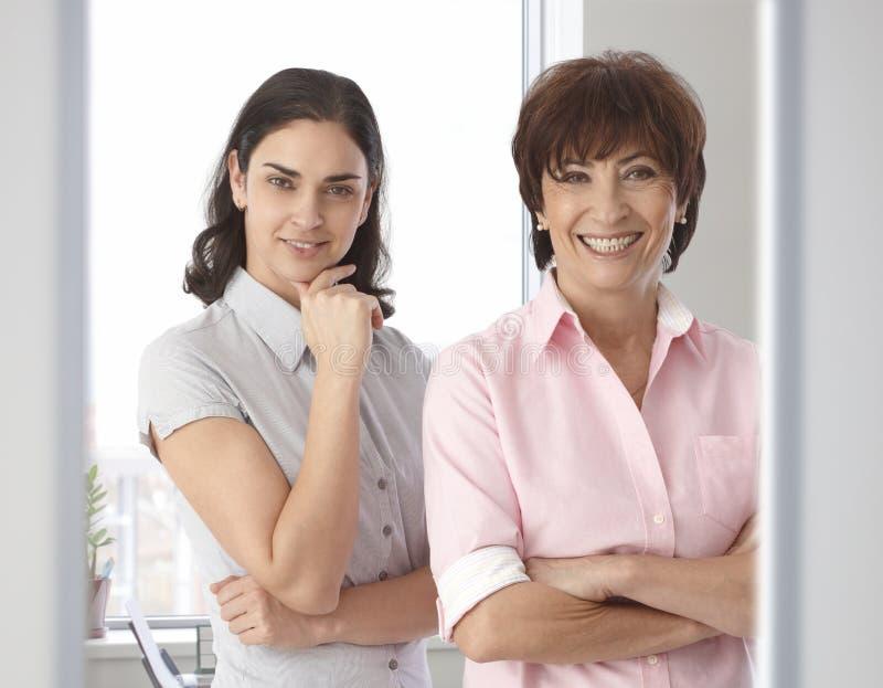 Lyckliga tillfälliga kvinnliga affärskontorsarbetare royaltyfria bilder