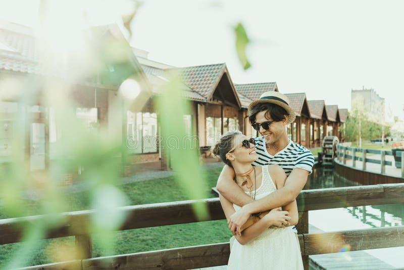 Lyckliga tillfälliga par som kramar, medan stå på bron nära stugabyggnader fotografering för bildbyråer