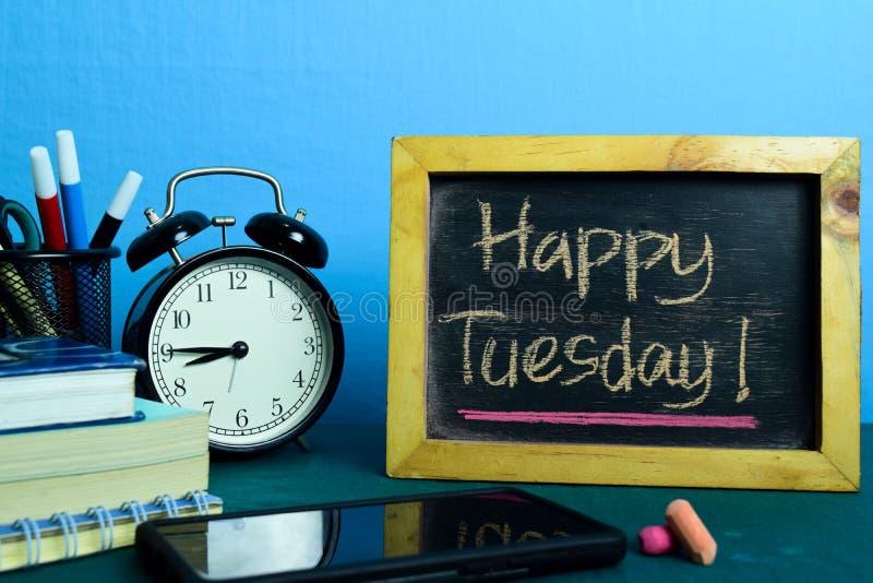 Lyckliga tisdag! Planläggning på bakgrund av arbetetabellen med kontorstillförsel arkivbilder