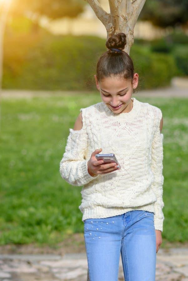Lyckliga tonåriga barnarbeten i telefonen som ser in i den, betalar gods royaltyfria foton