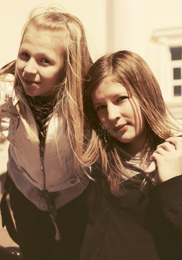 Lyckliga tonåriga flickor på stadsgatan arkivbild