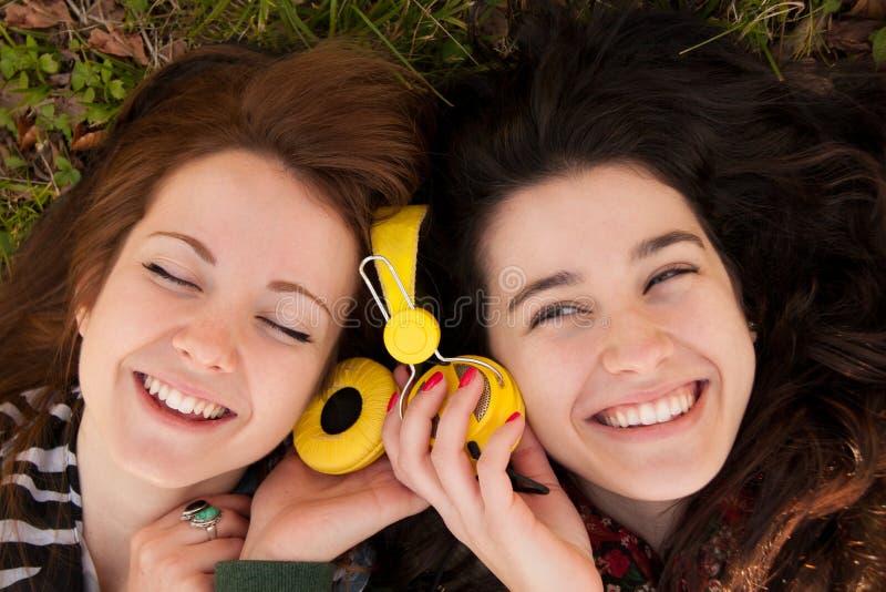 Lyckliga tonåriga flickor som delar musik royaltyfria foton