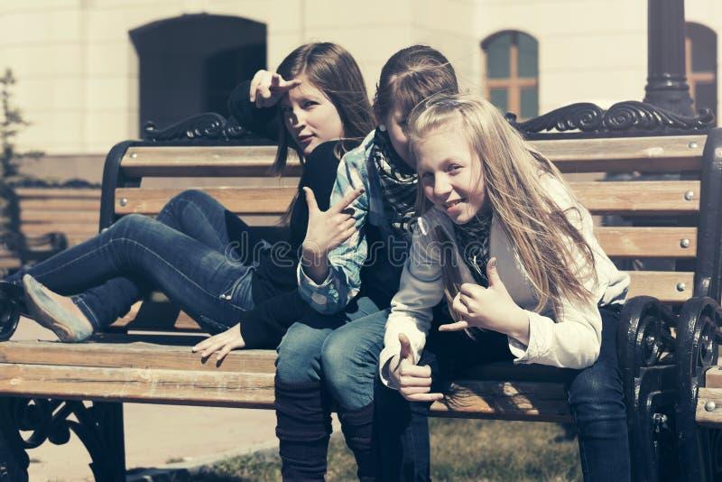 Lyckliga tonåriga flickor som sitter på bänk i stadsgata royaltyfri fotografi