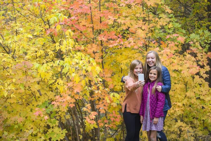 Lyckliga tonåriga flickor som tar selfie parkerar in royaltyfria bilder