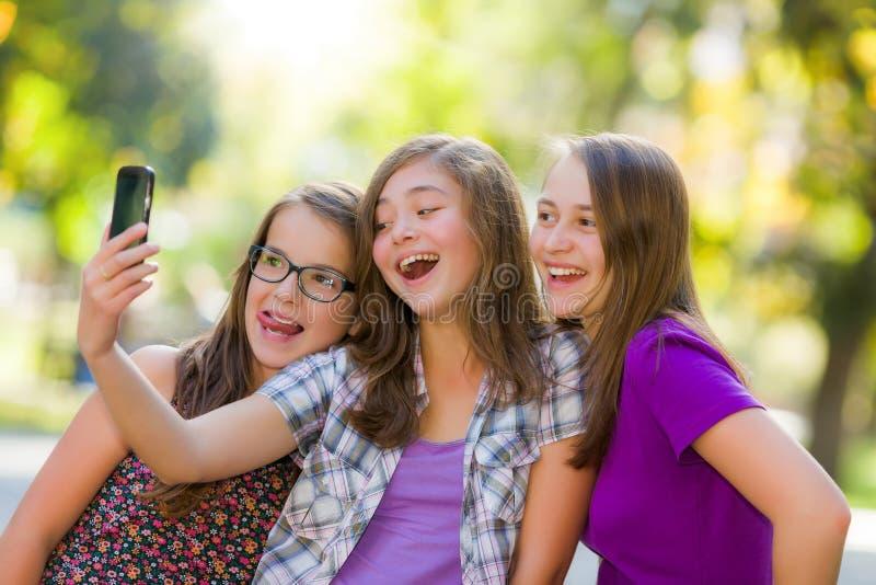 Lyckliga tonåriga flickor som tar selfie parkerar in arkivfoton