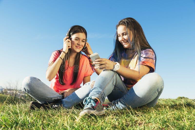 Lyckliga tonåriga vänner i sommar parkerar lyssnande musik royaltyfria foton