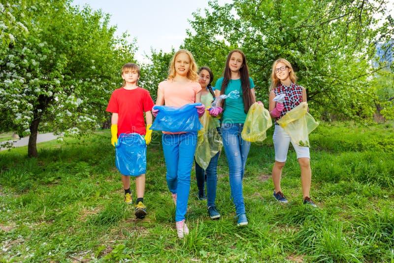 Lyckliga tonåringar bär handskar och bär avskrädepåsar royaltyfria bilder