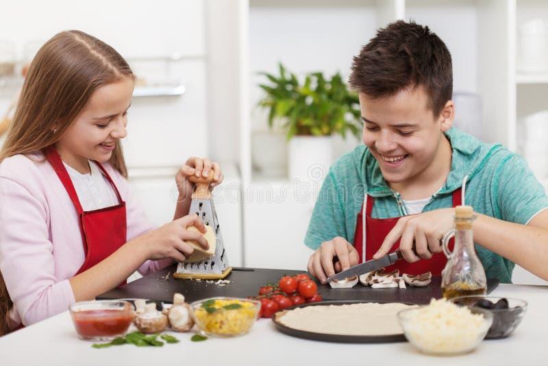 Lyckliga tonåringar som har gyckel i köket som förbereder en pizza arkivbild