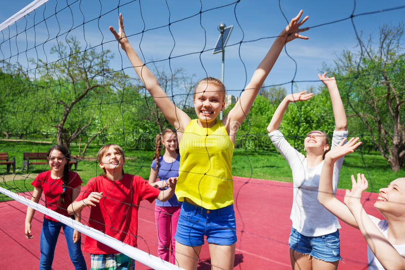 Lyckliga tonåringar som netto spelar nära volleybollen arkivbilder