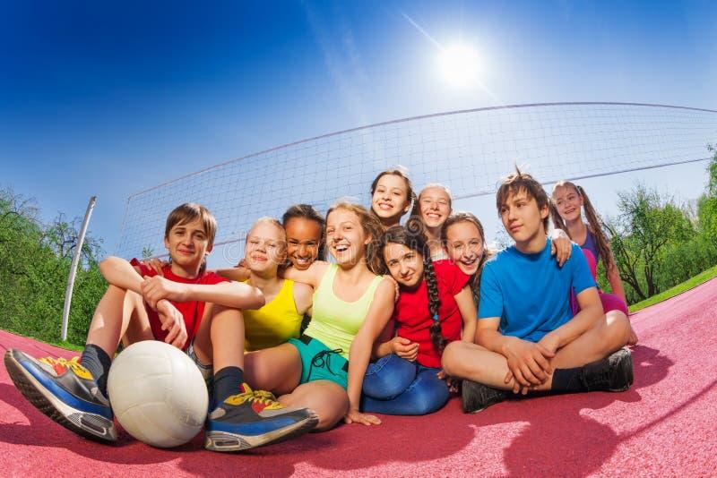Lyckliga tonåringar som sitter på domstolen för volleybollleken arkivfoton