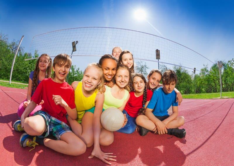 Lyckliga tonåringar som sitter på volleybolldomstolen arkivfoton