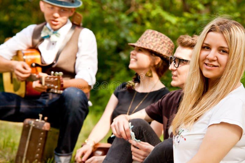 Lyckliga tonåringvänner som sjunger vid gitarren i parkera royaltyfria foton