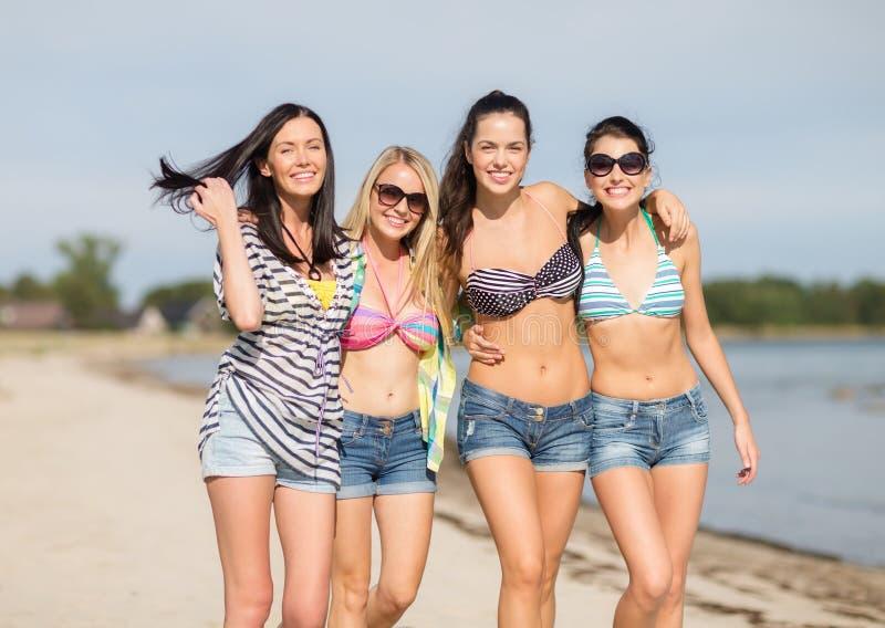 Lyckliga tonårs- flickor eller unga kvinnor på stranden royaltyfria foton