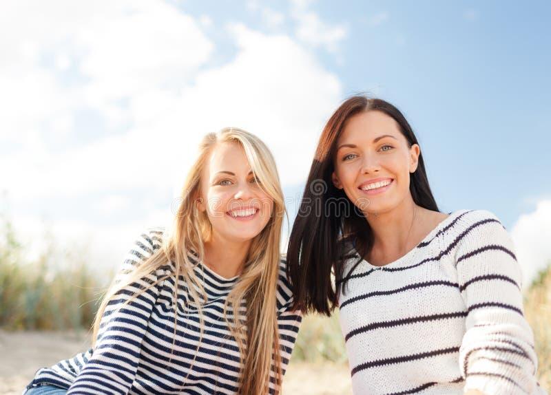 Lyckliga tonårs- flickor eller unga kvinnor på stranden royaltyfria bilder